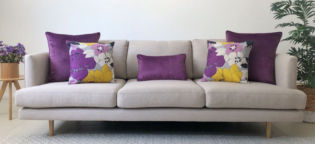 Purple floral and block coloured cushions in different sizes on a grey sofa.