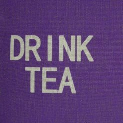 Close up of linen purple cushion with drink tea written on it