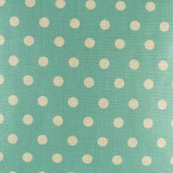 Zoomed in view of teal polka dot pattern on cushion cover
