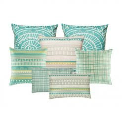 A set of seven teal and white square cushion covers with linear, abstract and triangle designs