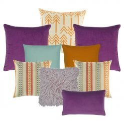A mix of plum, orange, lilac, teal and multi-colored square and rectangular cushions with arrow and line patterns