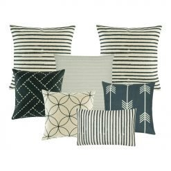 A set of 7 cushion covers in navy and neutral colours with stripes, cable knit, arrows and circle patterns
