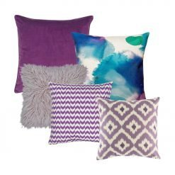 One light violet cushion with diamond patterns, one purple and white cushion with zigzag design, one abstract design cushion, one fur cushion in lilac and one plain purple cushion