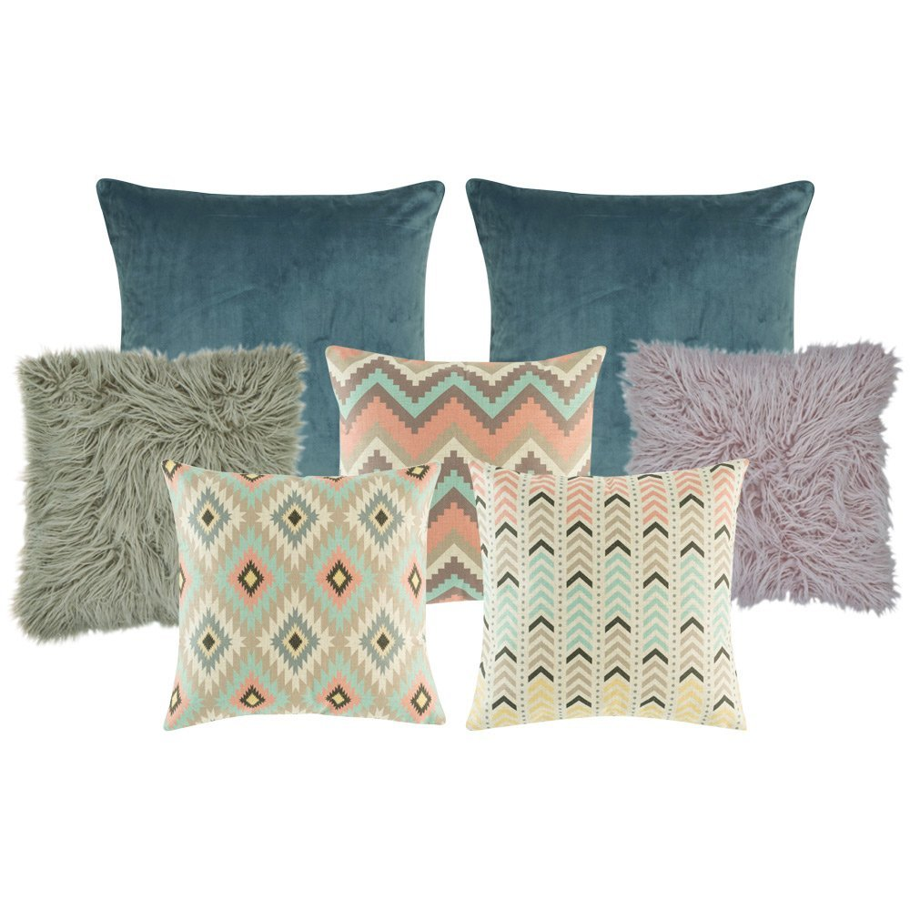 A collection of 7 square cushions with blue, grey, lilac, teal colours and with diamond and arrow patterns