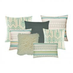 A collection of seven cushions in teal, grey and white colours with arrow designs