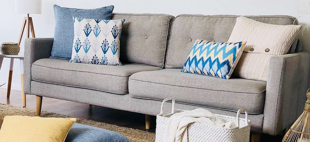 A coastal styled scene with blue and beige cushions on a grey sofa