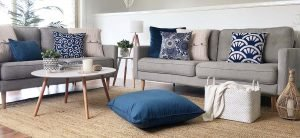 Living room decorated with different kinds of cushions in navy blue and cream colours.