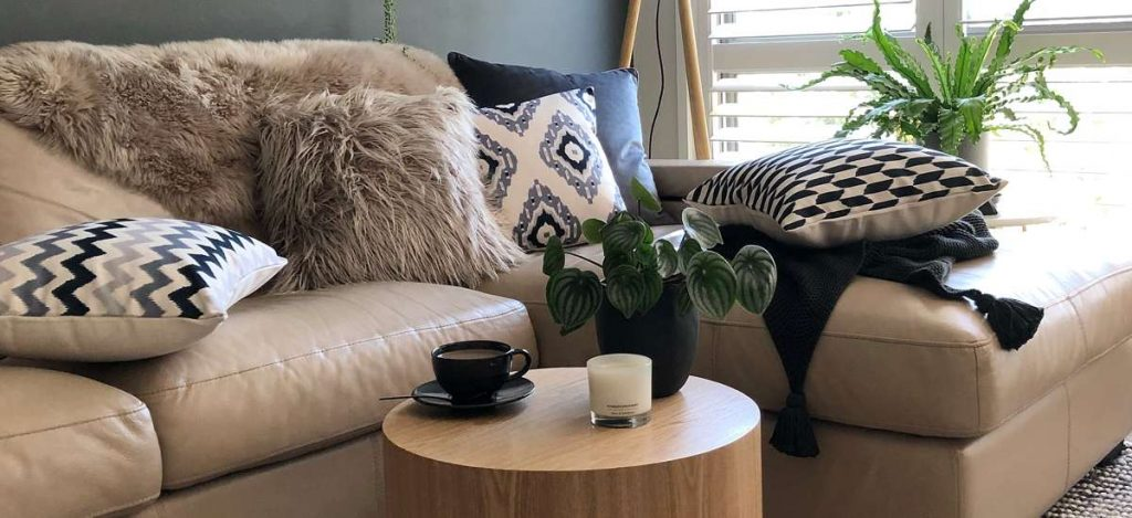 5 Pieces of white and grey fur and patterned cushions on a sofa.