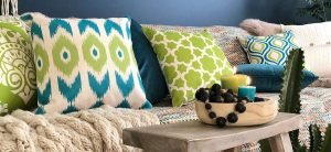 Green and blue patterned cushions to accentuate the blue walls and the multi coloured sofa.