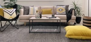 Patterned cushions in mustard and grey and a floor cushion is used to give the room a homier vibe.