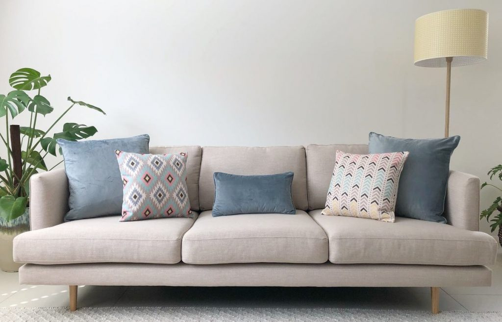 Neutral sofa with soft blue and pink cushions