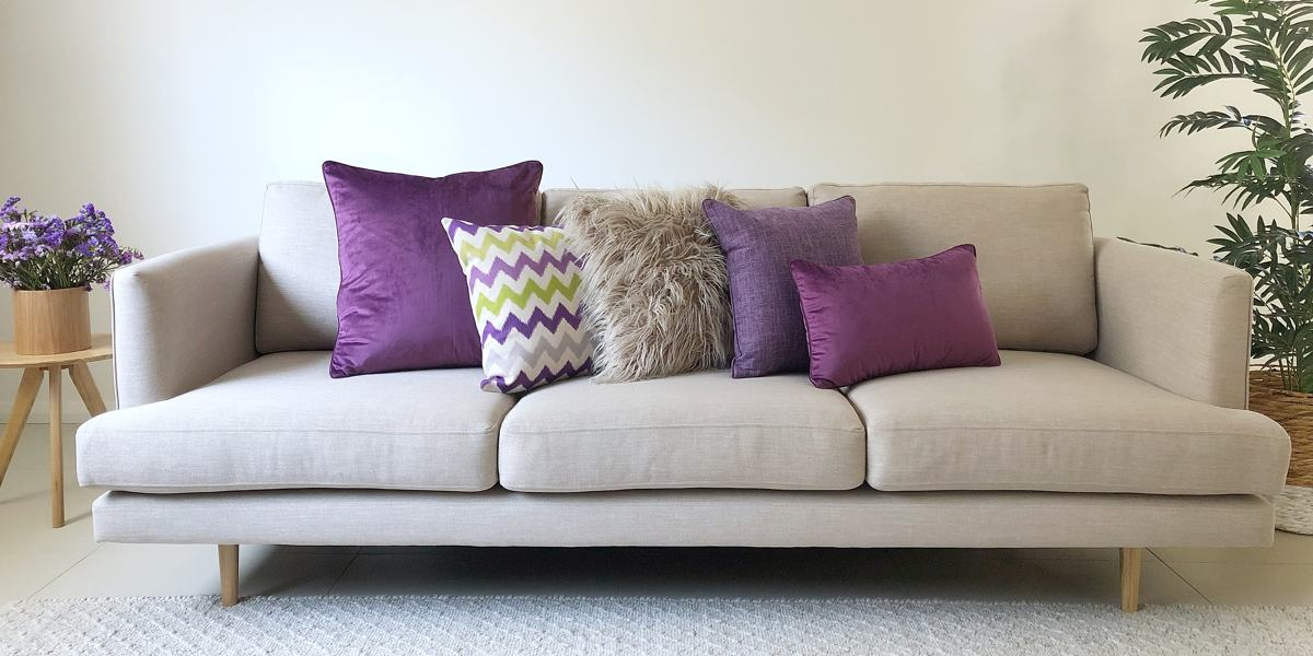 A grey sofa with 5 cushions in all different textures