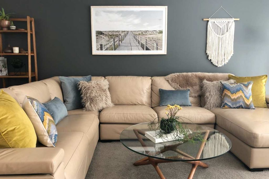 A corner sofa with decorative cushion in multiple texture and patterns in light blue and mustard colours.