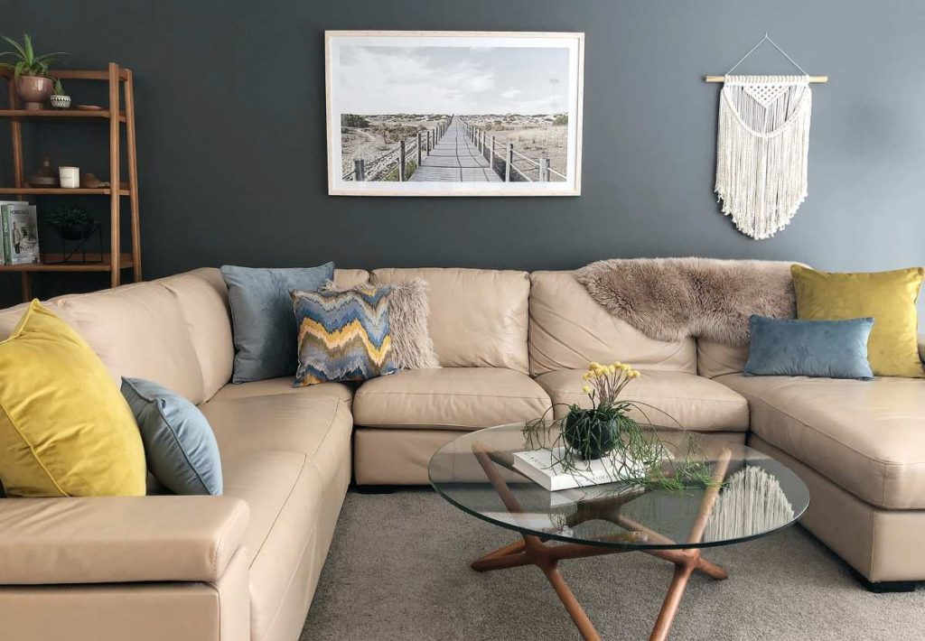 Corner sofa with mustard, soft blue velvet textured cushions