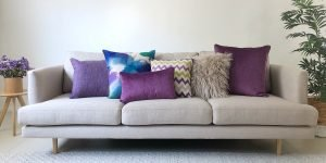 A collection of cushions in different texture, shapes and sizes in purple hues.