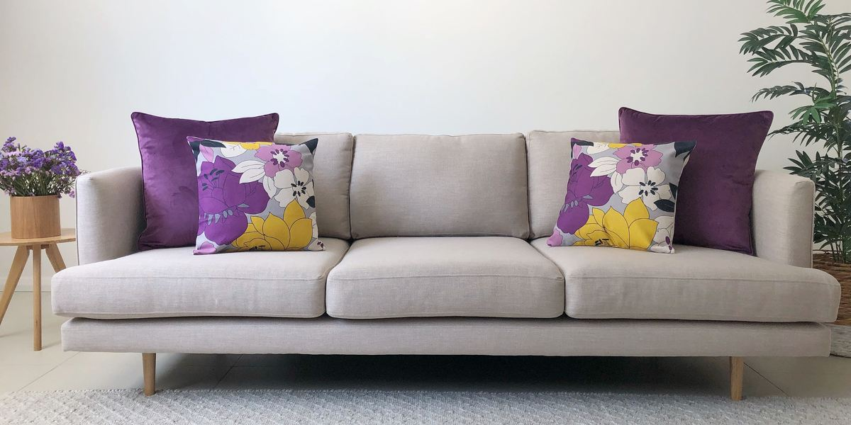 A grey sofa in a living room with a standard 2 2 cushion arrangement