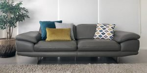 An arrangement of 3 in 1 cushions in mustard,blue and grey and a patterned cushions softens the appearance of the grey leather sofa.
