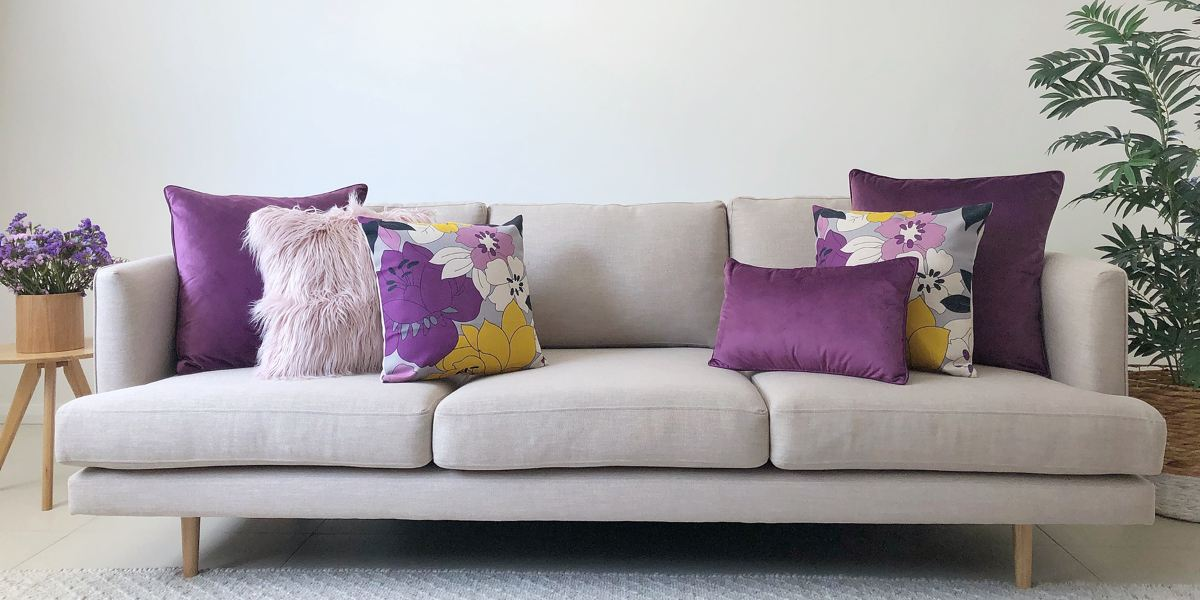 A grey sofa with 6 cushion sin purple, pink and yellow colour palette