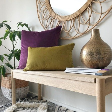Hallway table with purple and mustard velvet cushion covers with styled indoor plant and mirror
